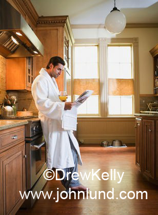 Man Standing In Kitchen At Home Leaning Against Stove Reading a ...
